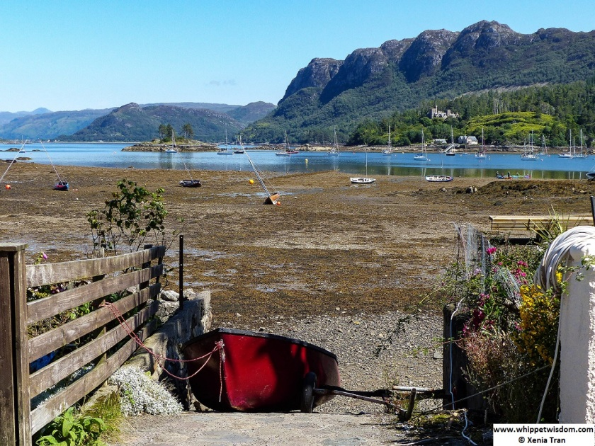 low tide in Plockton Bay, red rowing boat tied to a ramp