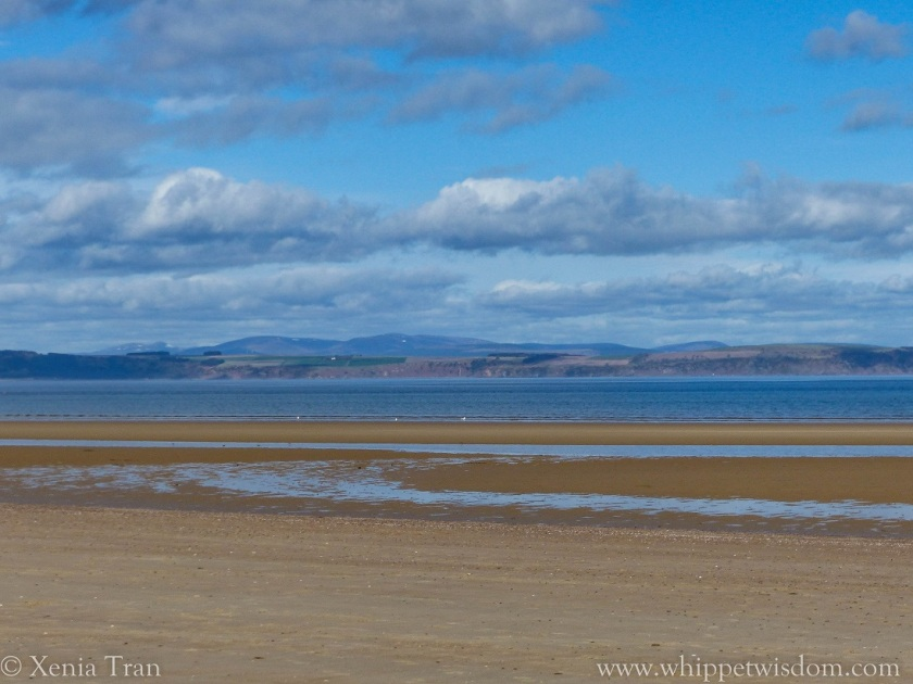 beach at outgoing tide with hills across the firth