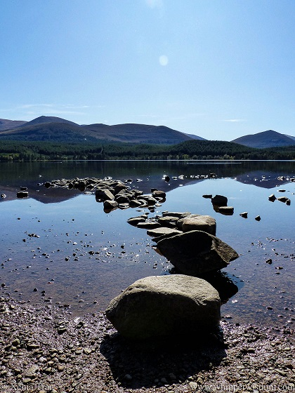 a row of stones in the loch curving towards the mountains