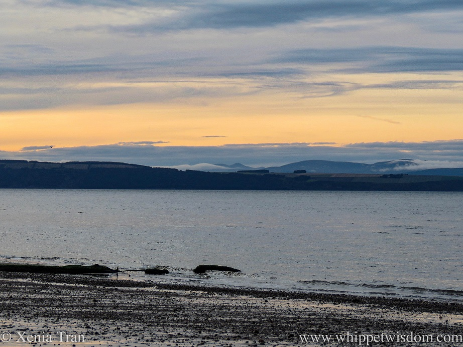 sunset across the Moray Firth, a golden sky over blue mountains