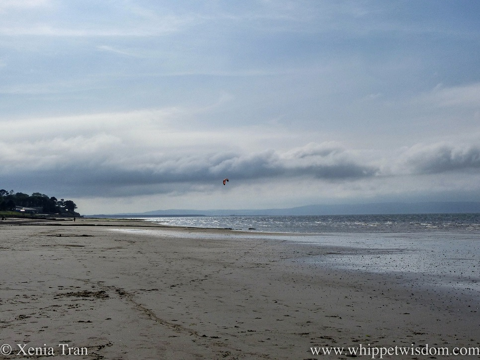 a beach at dusk with a distant kite surfer on the silver sea