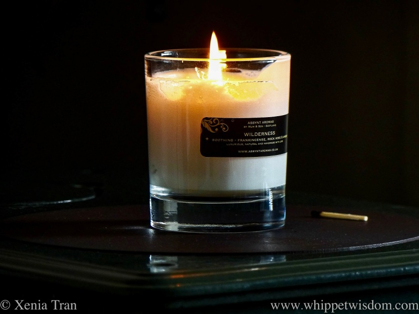 close up of a assynt aromas candle in a class