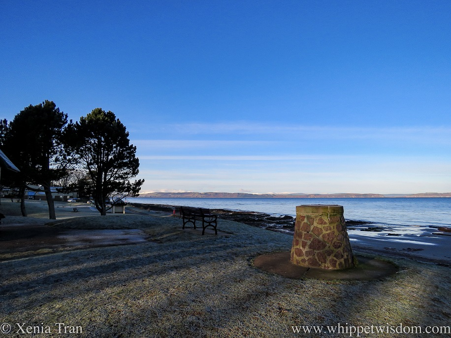 a cairn and bench overlooking the Moray Firth with snow on the peaks across the water